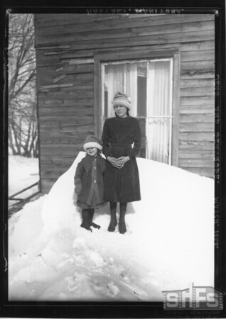[Gertrude and Gene in front of a house]