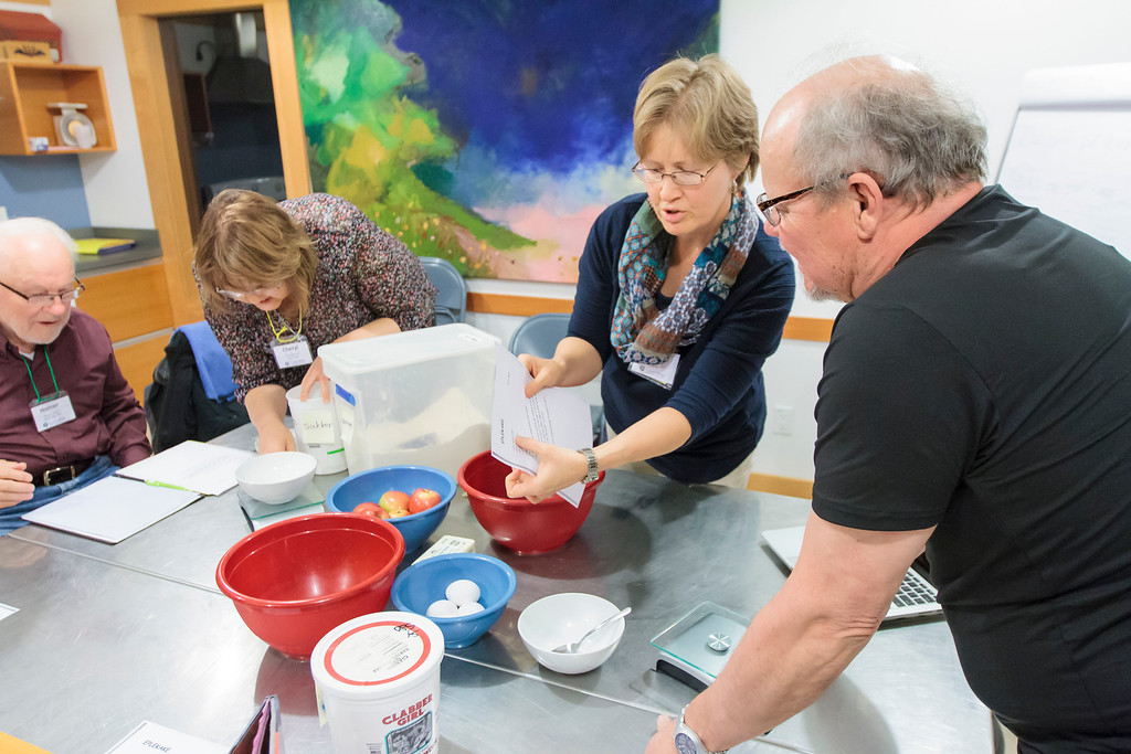 Adult learners of Norwegian work to understand the recipe during a cooking activity.