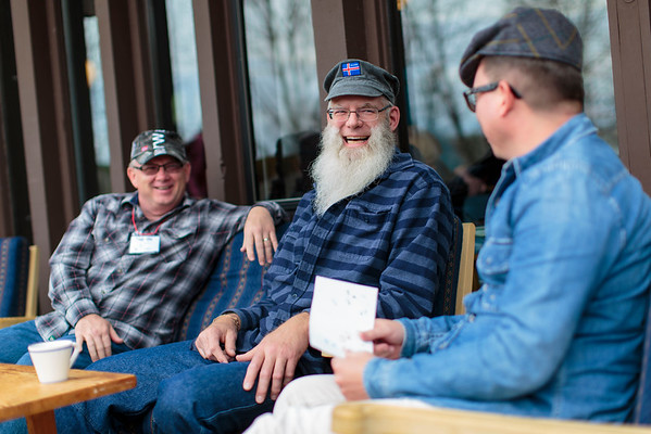 Three men, adult learners of Norwegian, laugh together in the sunshine.