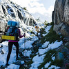 Young woman with backpacking gear and a dog hike through a snowy pass in the Ansel Adams wilderness