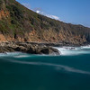 Long exposure of deep blue water, swirling surf, and rocky cliffs of central California