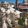 Stone sculpture in garden around a Victorian mansion