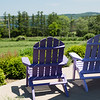 Two lavender painted adirondack chairs  on a porch overlooking farm fields