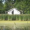 Tent cabin in the woods next to pretty pond and grasses