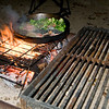 Cooking salmon seasoned with pesto and broccoli on the campfire