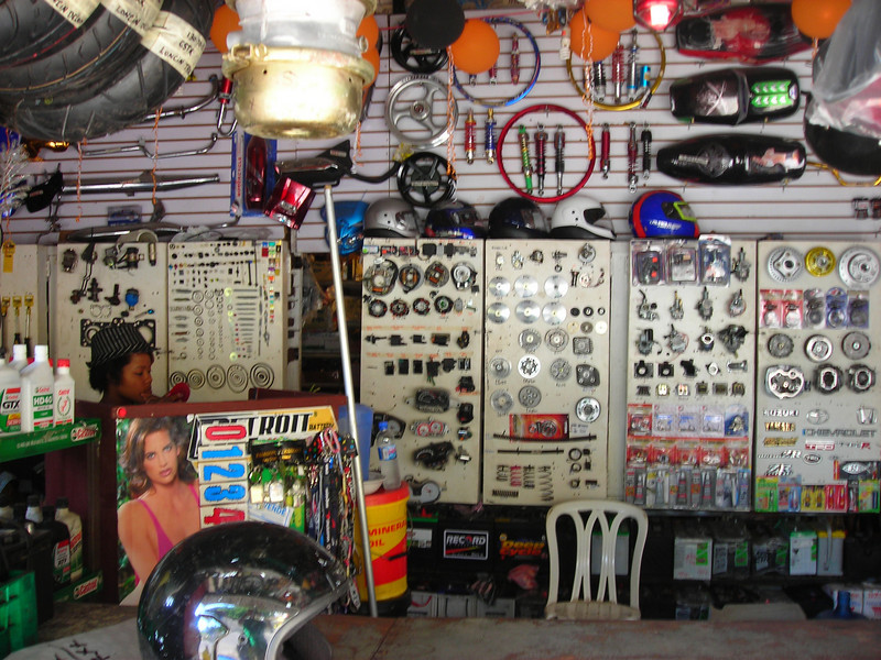 "Before I take off with Heidi on a ride round the island, I need to get a rearview mirror. I get up early head West along the coast to Los Charamicos, a small Dominican village along the highway. This is where I go for all my motorcycle needs. It is just a small parts store with a shop attached. If you don't speak Spanish here you are out of luck. I look up the Spanish words for 'rear view mirror' before I head out. I write it down on paper in case I forget. And by just writing the words down is a great way for me to remember them. I start out with my most proper Spanish. ""Good morning sir. How are you doing?"" ""I am looking for a rear view mirror for my motorcycle"" I explain how I have no hole to mount the mirror and that I need a mirror with a universal mounting bracket to clamp to my handlebar."