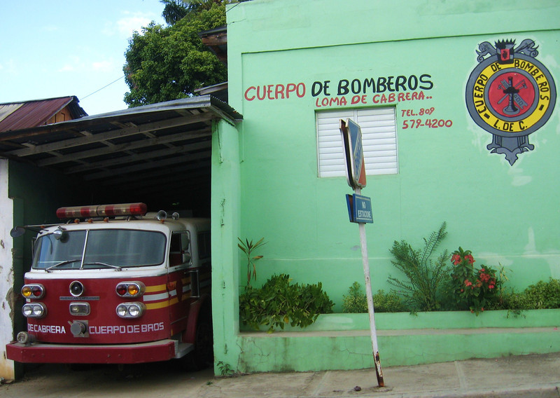 A modern looking fire engine at a crossroads village in the mountains.
