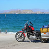 42 miles down a dead end road to Bahia de Los Angeles. Heidi has read about this place, it sounds just like the kind of place we like. Small village on the Sea of Cortez with fishing and sailboats. We plan on spending a few days here and sort out our situation. More desert, mountains and cacti:<br /> <br /> There is no traffic now and the road is straight. Now I have time to think about what the heck is going on with our bike. I formulate a theory why the bike is starting back up after quitting, but it doesn't explain why the bike quits. We ride on….<br /> <br /> Again I'm not making any of this up. We are tooling along less than 20 miles from the Sea of Cortez and the bike just quits again. We coast to a stop, dismount, take off our helmets and look at each other 'This can NOT be happening'<br /> I stay calm, confident of my theory. After a few minute wait I hit the starter. The bike fires up as if nothing has happened. We hop back on and continue. Bahia de Los Angeles here we come.<br /> <br /> <br /> <br /> We made it. In my mind I bend down to kiss the Sea. This is what we dream about, places like this.