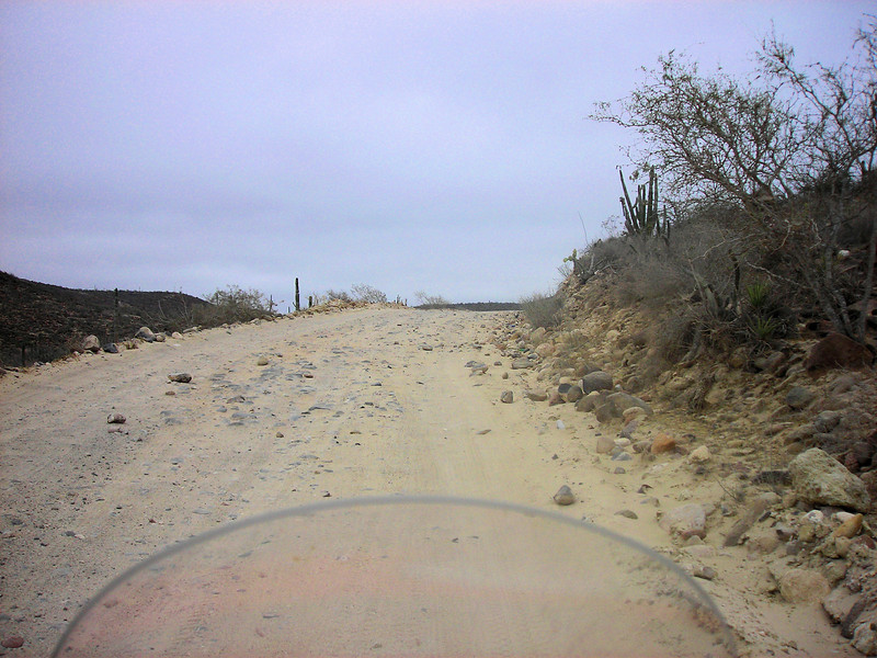 The 20 miles of dirt road south of town didn't get any easier to ride. I kept the speed way down which helps on the washboards but makes the deep sand more difficult. Sometimes in deep sand we fishtaile from one side of the road to the other before bringing it under control. The greater speed causes increased inertia on the wheels which make the wheels track better in deep sand. This was not fun with my precious cargo on back so I keep it slow anyway. If we are going to 'dump it' it will be a slow dump.<br /> <br /> During one rest stop this truck with locals stopped to make sure we don't need any help. That makes us feel great knowing that even out here in the middle of nowhere we can get help if we need it.