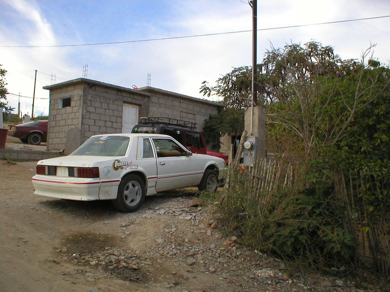 Mexican Mechanic:<br /> I'm off on the two mile hike to Cristian's house where my jeep will be ready. His sister has a house just like this behind his with a court yard in between. Mari's house is just up the hill. Cristian does all his work along side his house. He recently bought a lot up the road on a hill for $1,800 and is going to have a new house with several car stalls for his business.