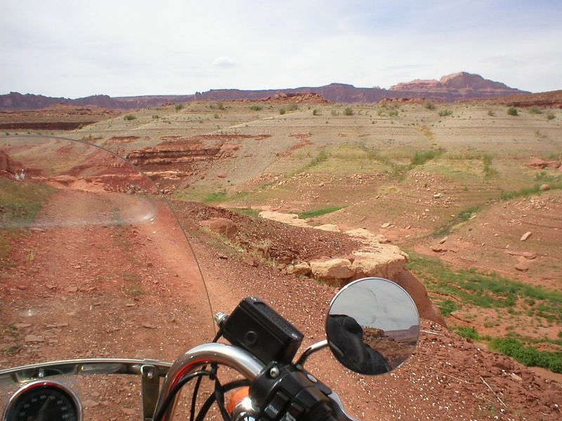 """I was talking to some other bikers and I mentioned water. One of then said """"Lake Powel, 75 miles up"""", cool. I see the lake Powel sign, it directs me up a dirt road 3 more miles. I head up the dirt road. 3 miles later it started getting real rough. I meet a jacked-up 4WD pickup with the back filled with blow up rafts, coolers, fishing stuff and a bunch of kids. We pull up along side each other and I ask the intelligent question, """"Is there any water down there?"""" (da!) he says """"ya, if you can get to it"""" so I say """"What, is it that tough?"""" he looks at me  """"Naa, you can do it, there's two trucks, no, now just one truck back there"""" """"OK, thanks"""" we all wave good bye."""