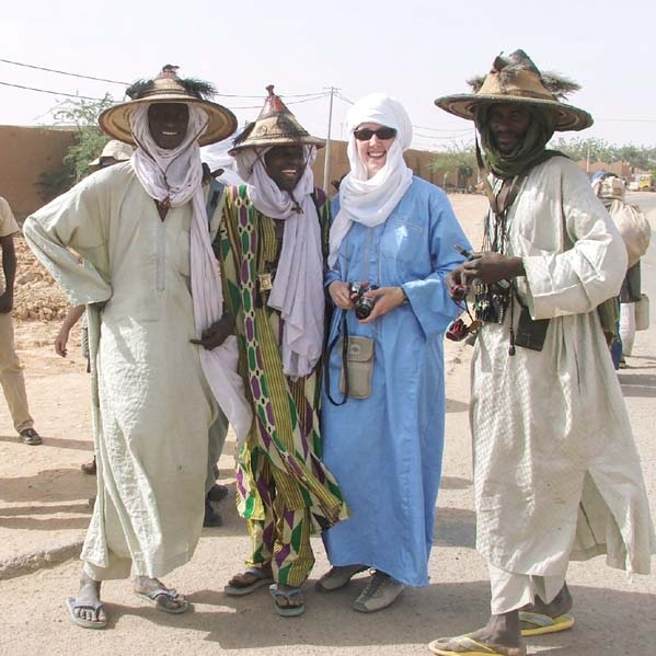 """Day 8<br /> Sunday 2 April 2006<br /> <br /> We spend the morning on a walking tour of Agadez with Eissa, Bibi and our drivers.  To the camel market, which was mostly goats and donkeys, and then through the main sundries market again.  My contacts were still bothering me, but I managed to grab a fair amount of video nonetheless.  <br /> <br /> Lunch at the same restaurant as Saturday night, but this time in a low slung tent structure in the back of the main building.  Covered with canvas and carpets and with the ground underneath covered with carpets and cushions lined along the sides - it was a very comfortable, not too hot space.  Lots of flies inside though; Rei trapped hundreds of them inside a disused Niger beer bottle, baited with Le Pain!  Afterwards they all congregated on the uneaten orange slices, for a colourful and high contrast photo op!<br /> <br /> After lunch I shared a car with Colin, who dropped at a nineteenth century German explorer's house, then I went on to the internet shop for a half hour.  A small mud brick building,  but thankfully with air conditioning!  Able to check my Goggle mail after a while fiddling with the euro-centric keyboard where all the keys were a bit mixed up.  The """"crunchy"""" feeling also didn't help, as the keyboard was pretty well filled with sand!<br /> <br /> Missed my rendezvous time with Bev, Rei and Erland, but made my way to the market nevertheless, and of course found them within a few minutes.  Turns out Agadez wasn't QUITE the bustling metropolis that we had expected after all.<br /> <br /> They were picking up a Tuareg outfit that they had ordered to be custom tailored the day before - for Will's birthday.  It was quite enormous, (for a 10 year old, not 3), but none of us had the sense to have alterations ordered then and there….<br /> <br /> Spent some more time walking through the market, picking up some new printed cloth for shirts for myself, (""""heartbreak phone call"""" & """"dismembered fingers with third eye"""" patt"""