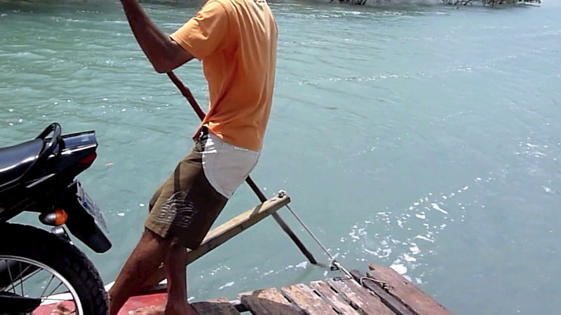 Crossing the Lagoa das Guarairas, by hand poled barge,south of Natal, Brazil