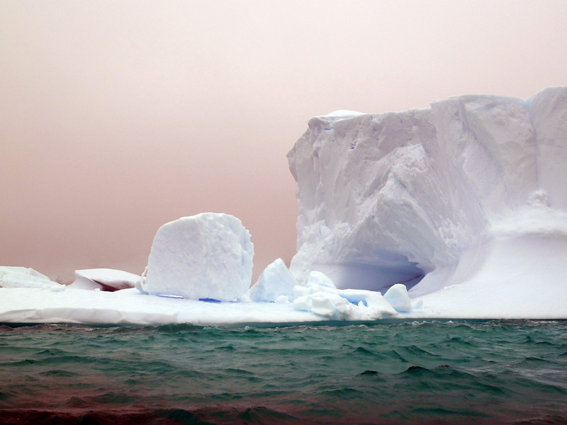 "Cave and loose cube form on a floating iceberg in the ""Icebergs Graveyard"" in the Penola Strait near Booth Island, Antarctic peninsula"