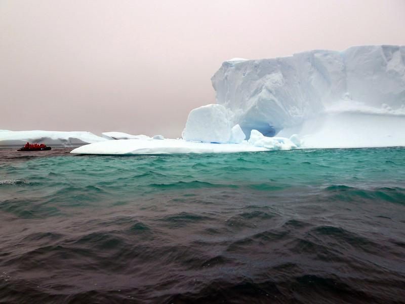 "Scale comparison of massive iceberg to the zodiac boat on left in the ""Icebergs Graveyard"" in the Penola Strait near Booth Island, Antarctic peninsula"