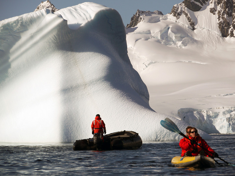 Kayakers amongst massive icebergs in the bay at Cuverville Island, mainland Antarctic peninsula