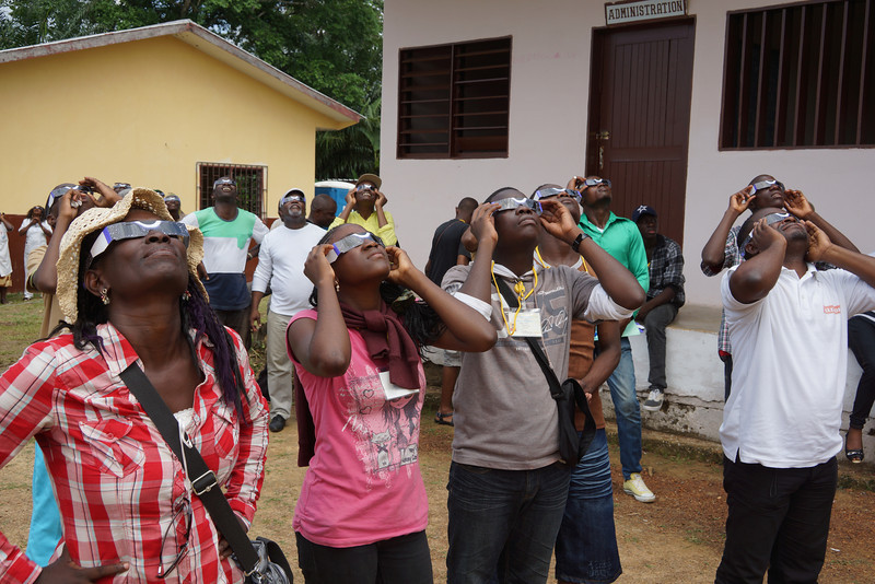 City dwellers down from Libreville for the day, mix with local villagers to chase the eclipse with the rest of us.