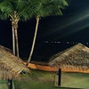 Oceanside atap cabanas are curiously empty at night.