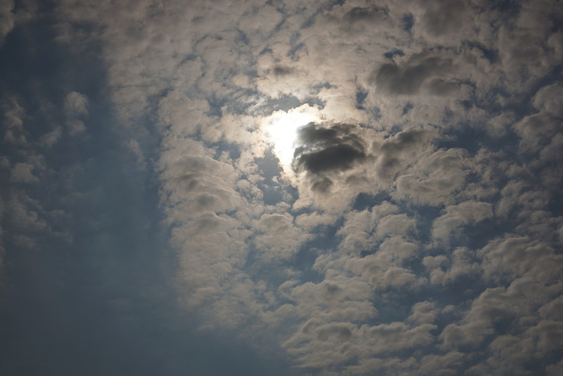 Heavy cloud cover resumes, obscuring the sun, as the partial eclipse wanes.