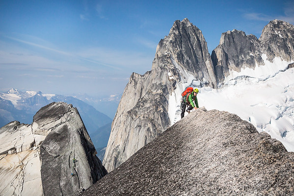 Gian leads an exposed ridge along Pigeon Spire in the Bugaboos. The unmistakable shape of the Howser Spires dominate the background.