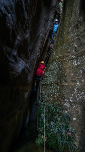 A very squeezy abseil from a small chockstone.