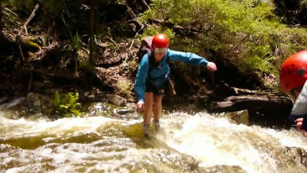 Rachel crosses the flooded creek above the next falls.