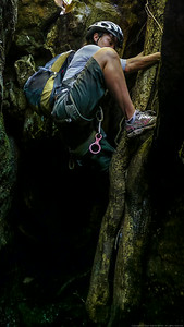 Angie climbs down a root ladder into the slot of the first canyon.