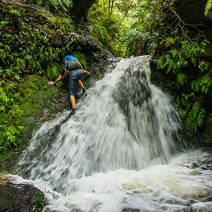 Carefully down climbing the waterfall.
