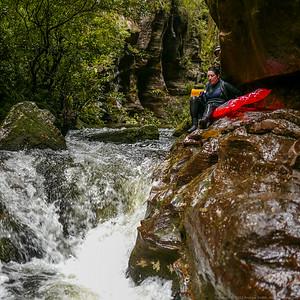 Jodi carefully slides along a ledge above a rapid.