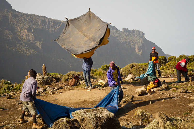 Porters shake the tents clean, and pack up camp before the ice crystals on the tents melt and soak through.
