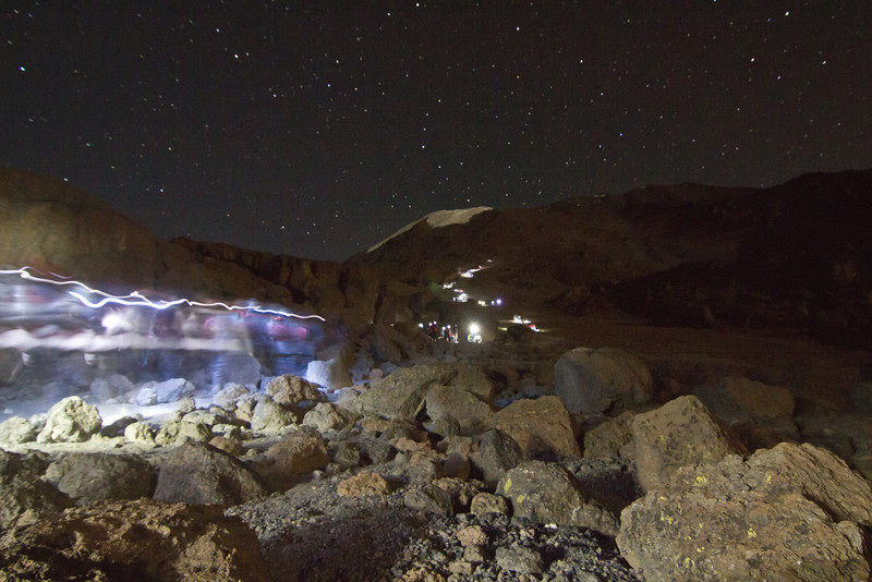 A train of light slowly snakes its way to the top of Kilimanjaro underneath the starry night sky.