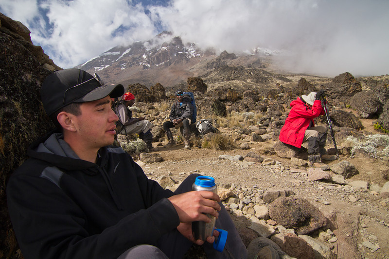 Sitting back in the rock shadow, Tom takes a drink in, while Maxine rests. Elias (the guide with the blue backpack) sits beside Zawadi and Maxine's daypack, which he was carrying for her. In these conditions, it is important to minimize the stress on the body and stay cool and hydrated in order to acclimatize better.