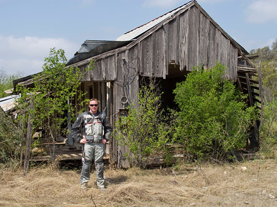 "Tommi earns his official ""Texas Adventure Rider"" title by having his pic taken by the old shack."