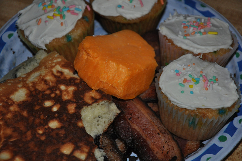 The breakfast mixture of bacon, pancakes, cupcakes, and a block of cheddar cheese