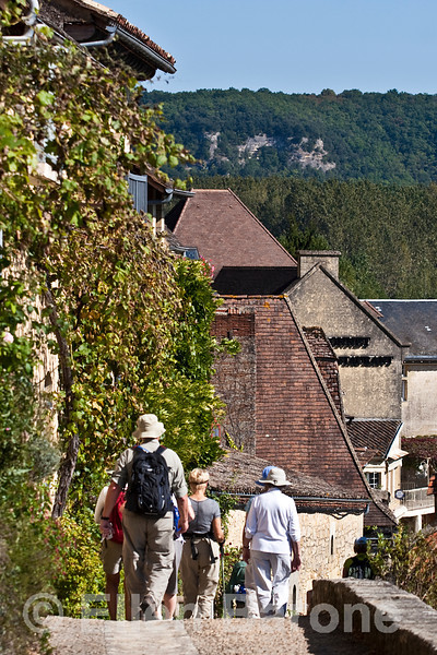Wayfarers walking in the cliffside village of La Roque Gageac, France
