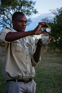 Pouring gin and tonic sundowners, &Beyond Xaranna Okavango Delta Camp, Botswana.