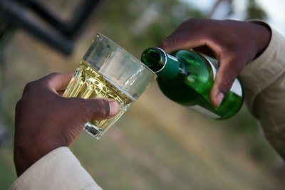 Pouring a glass of wine for sundowners at &Beyond Xaranna Okavango Delta Camp, Botswana.