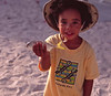 Adorable young Lawrence Wheatley, grandson to Lowell Wheatley, the founding owner of Anegada Reef Hotel, shows off his catch of the day, Anegada, British Virgin Islands (BVI), West Indies, Caribbean.