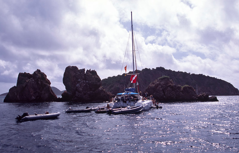 A commercial dive boat using the National Marine Park moorings to bring divers and snorkelers to The Indians, four large rock formations that rise from the ocean floor to a height of near 90 feet off Norman Island, British Virgin Islands (BVI), West Indies, Caribbean.