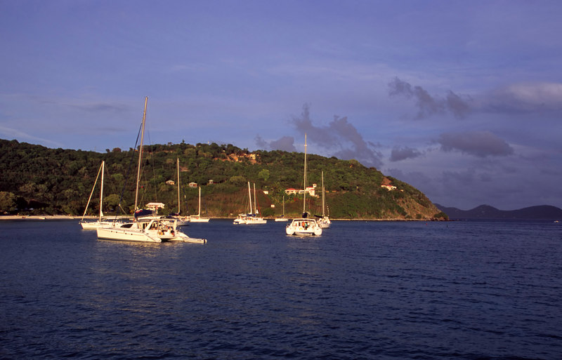The golden light of sunset casts a warm glow over yachts anchored in White Bay at Jost Van Dyke island in the British Virgin Islands (BVI), West Indies, Caribbean.
