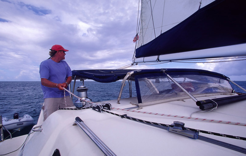 Charter Captain Warren Thring at work setting sails aboard The Moorings 45-foot sailing catamaran Triple Dog Dare, British Virgin Islands (B.V.I.), West Indies, Caribbean.