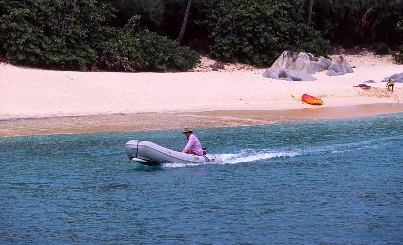 A yachtie in his dingy zips along the beautiful white sand beach at Spring Bay, adjacent to The Baths, Virgin Gorda, British Virgin Islands (BVI), West Indies, Caribbean