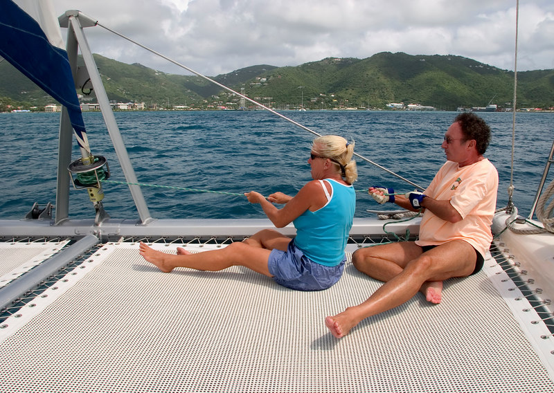 Charter chef/first mate Spike Shavers and pasenger Ken Sheppard pull in the jib sail aboard The Moorings 45-foot catamaran Triple Dog Dare, British Virgin Islands (BVI), West Indies, Caribbean.