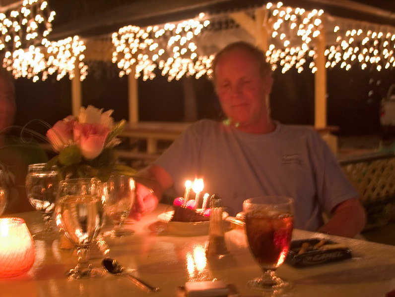 Charter Captain Warren Thring celebrates a birthday at The Lobster Trap restaurant, Anegada, British Virgin Islands (BVI), West Indies, Caribbean. Model release #0206.