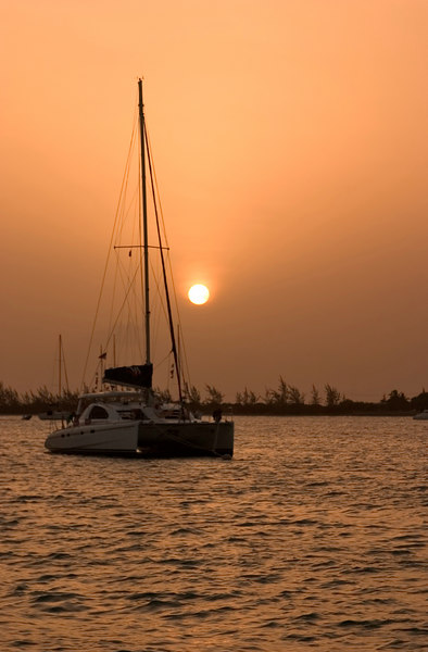 Moored sailboats silhouetted at sunset in the Anchorage off Anegada Reef Hotel, Anegada, British Virgin Islands (BVI), West Indies, Caribbean.