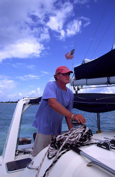 Charter Captain Warren Thring at the helm of The Moorings 45-foot sailing catamaran Triple Dog Dare, British Virgin Islands (B.V.I.), West Indies, Caribbean.