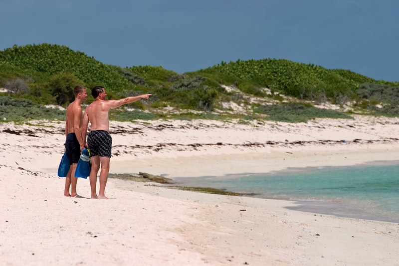 Snorkelers check out the conditions before entering the water on the beach at Loblolly bay, North Shore, Anegada, British Virgin Islands (BVI), West Indies, Caribbean.