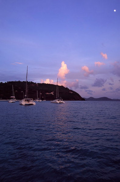 Early evening light and a full moon illuminate cotton-candy clouds and drapes an enchanting blue cast over White Bay, Jost Van Dyke, British Virgin Islands (BVI), West Indies, Caribbean.