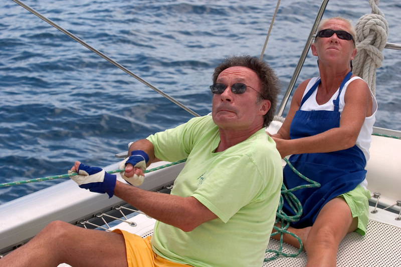 Charter chef/first mate Spike Shavers and pasenger Ken Sheppard aboard The Moorings 45-foot catamaran Triple Dog Dare, British Virgin Islands (BVI), West Indies, Caribbean. Model release #0054(Shaver) and 0208(Sheppard).