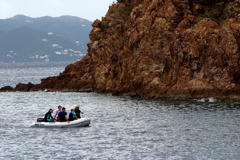 A dingy of snorkelers arrive at The Caves, a popular snorkel spot at Norman Island, British Virgin Islands (BVI), West Indies, Caribbean.